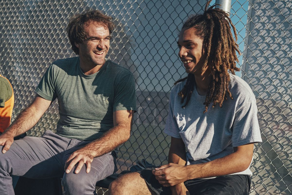 Soccer Without Borders founder Ben Gucciardi smiling on a bench with an athlete in front of a chainlink fence.