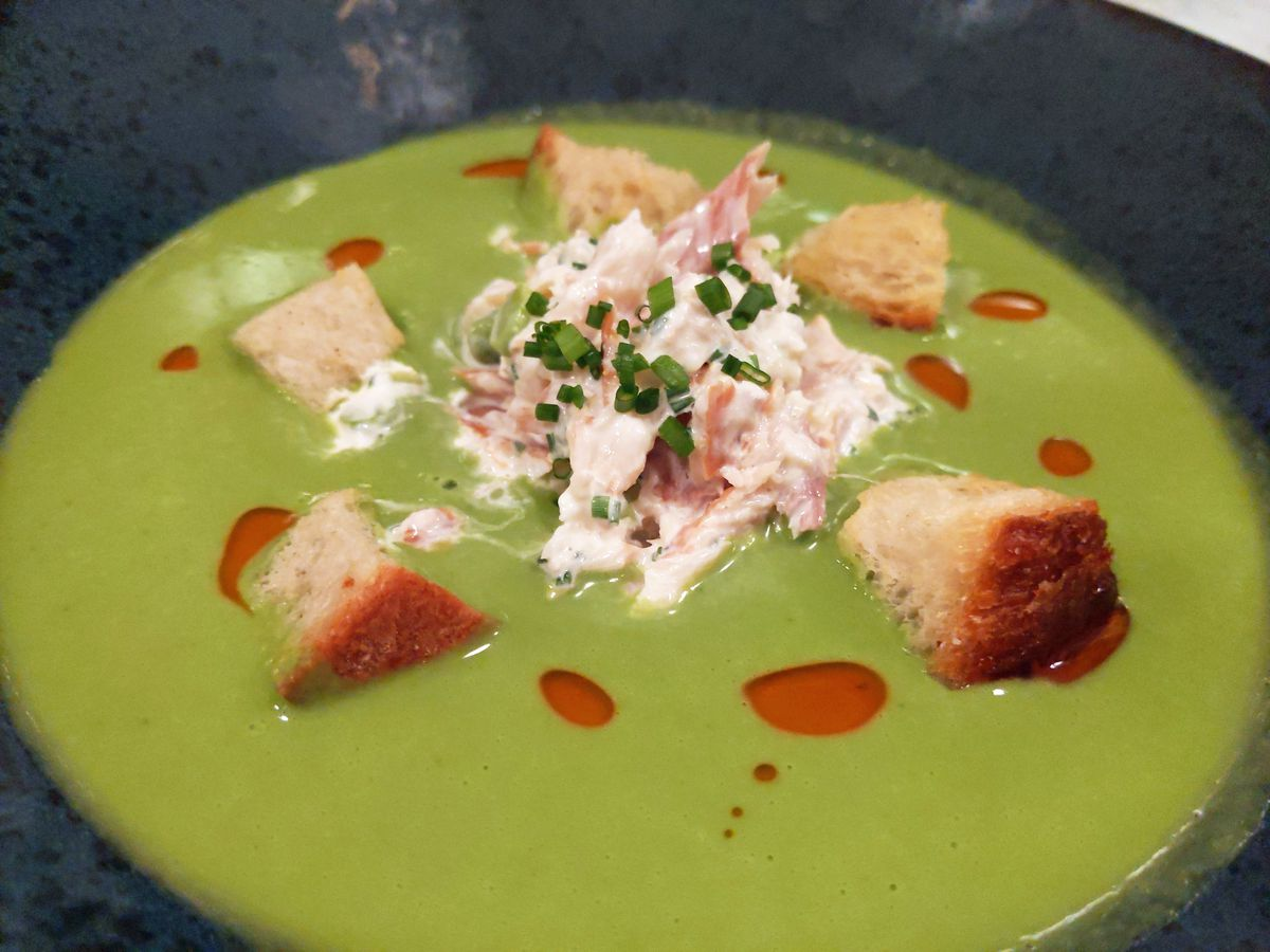 A bowl of green soup with wad of whitish smoked fish in the middle and a few croutons dancing around.
