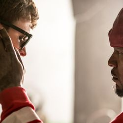 """Bats (Jamie Foxx) checks Baby's (Ansel Elgort) earphones as he's told by Doc why he always listens to music in """"Baby Driver."""""""