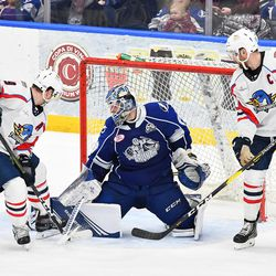 Syracuse Crunch goalie Eddie Pasquale (80) makes a save against Springfield Thunderbirds Harry Zolnierczyk (9) and Paul Thompson (15) in American Hockey League (AHL) action at the War Memorial Arena in Syracuse, New York on Saturday, December 29, 2018. Syracuse won 4-3 in OT.