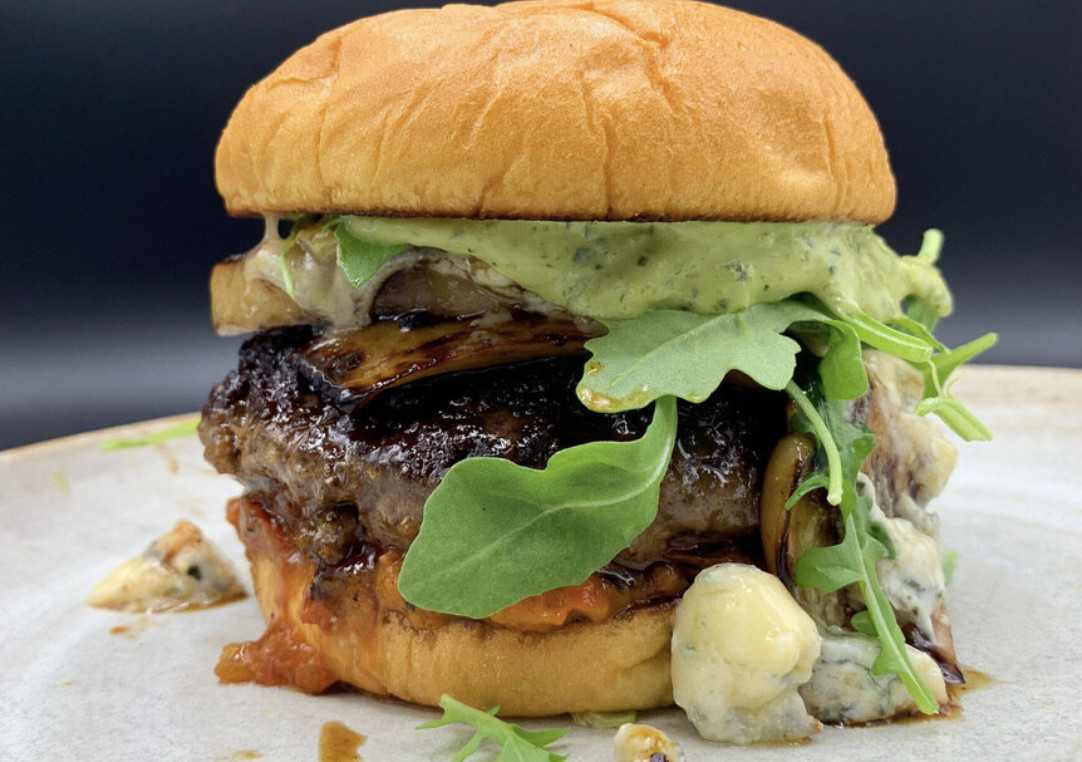 A large burger with topped with greens and blue cheese