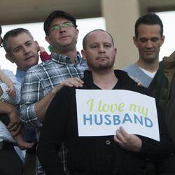 People listen and hold signs during a same sex marriage celebration at Library Square in Salt Lake City, Monday, Oct. 6, 2014.