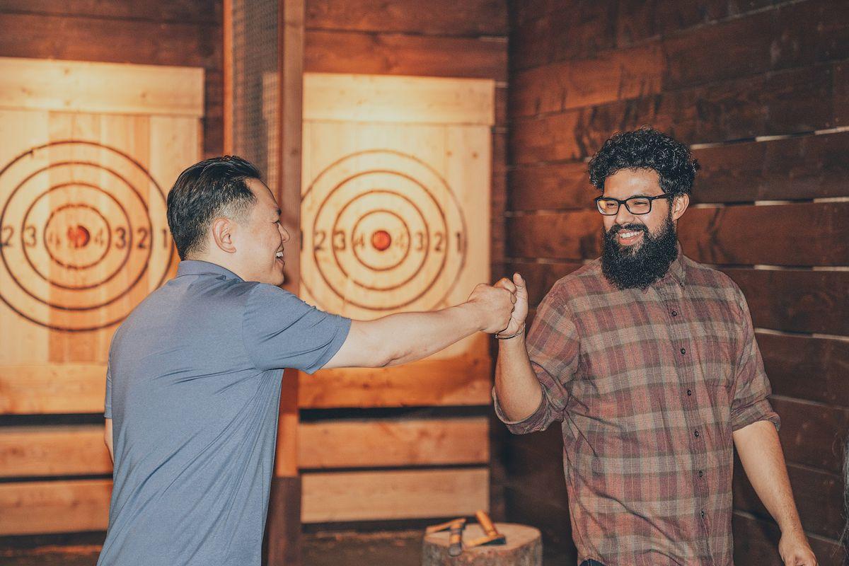 Two men at an axe throwing bar.