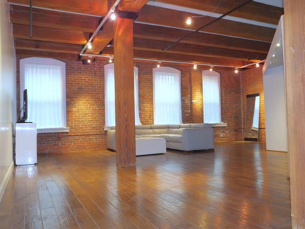 A cavernous open loft with high beamed ceilings and a sectional couch in the distance.