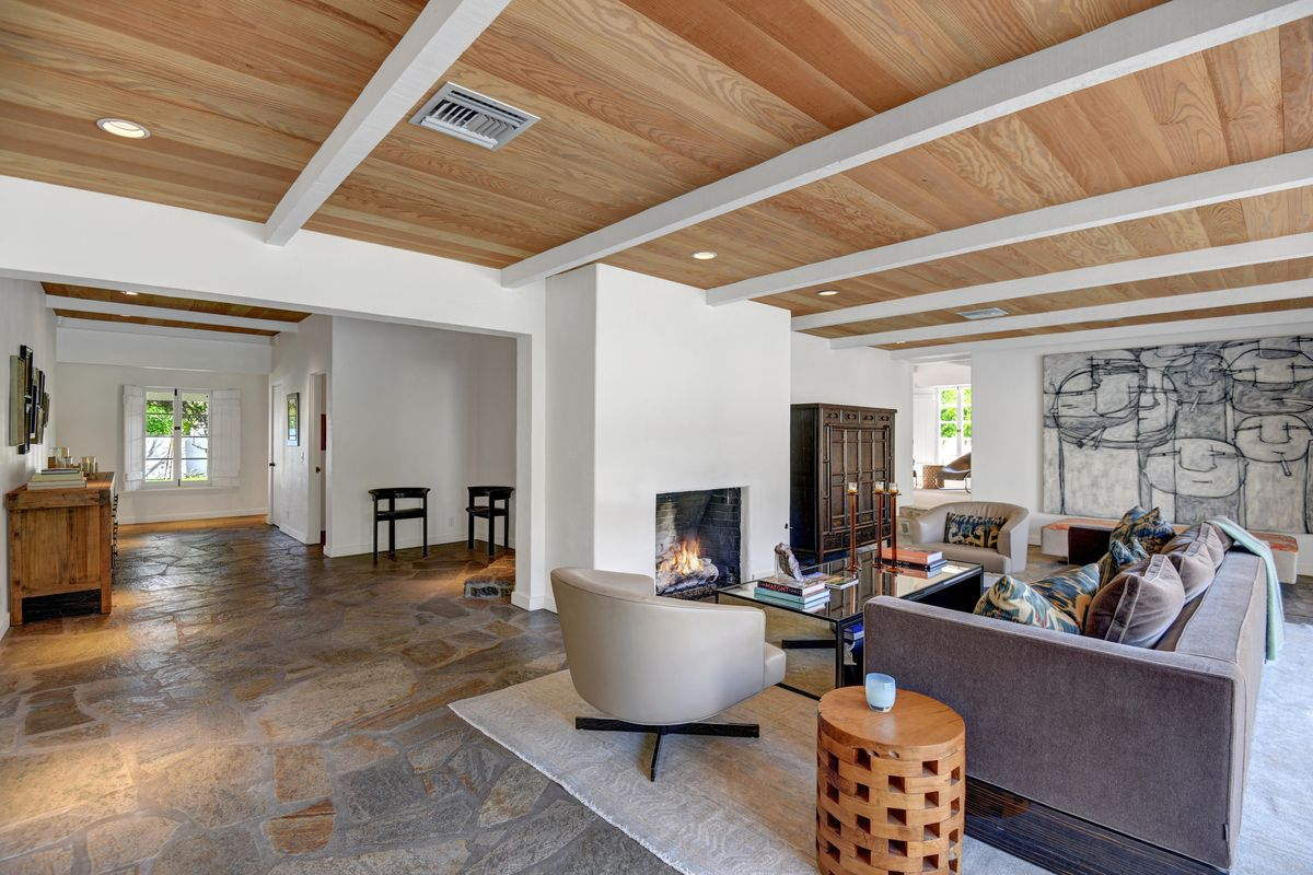 An open-concept living room has a fireplace, stone floors, beamed white ceilings, and seating area around the fireplace.