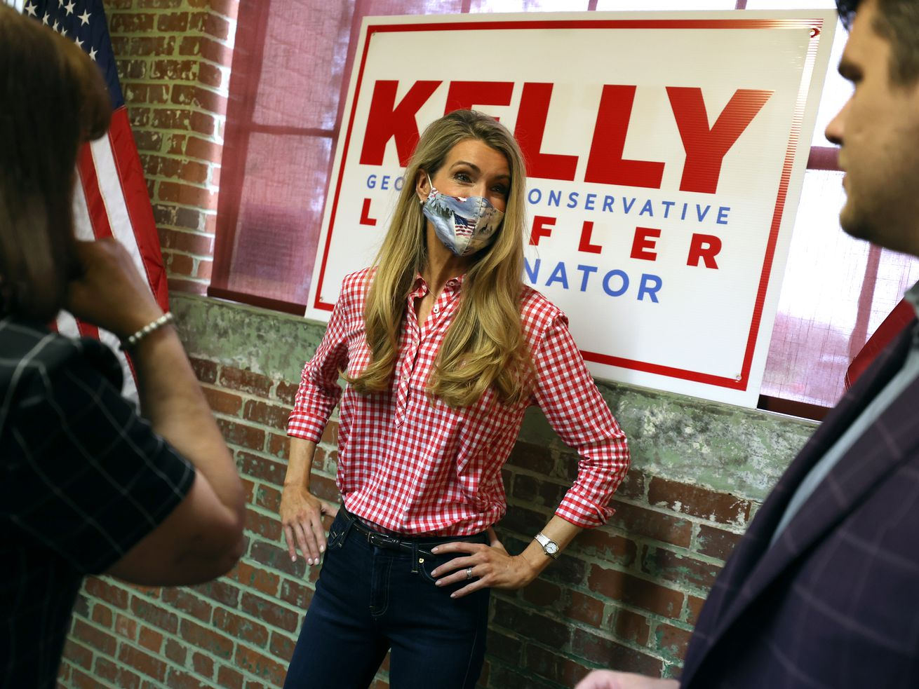 Loeffler, dressed in a red gingham shirt, dark jeans, and a blue mask, stands with her hands on her hips in front of a red and white sign bearing her name. A man stands to her left, and a woman to her right.