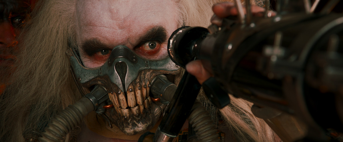 Immortan Joe with white hair red rings under his eyes and a metal cage housing his teeth, looks from behind a telescope