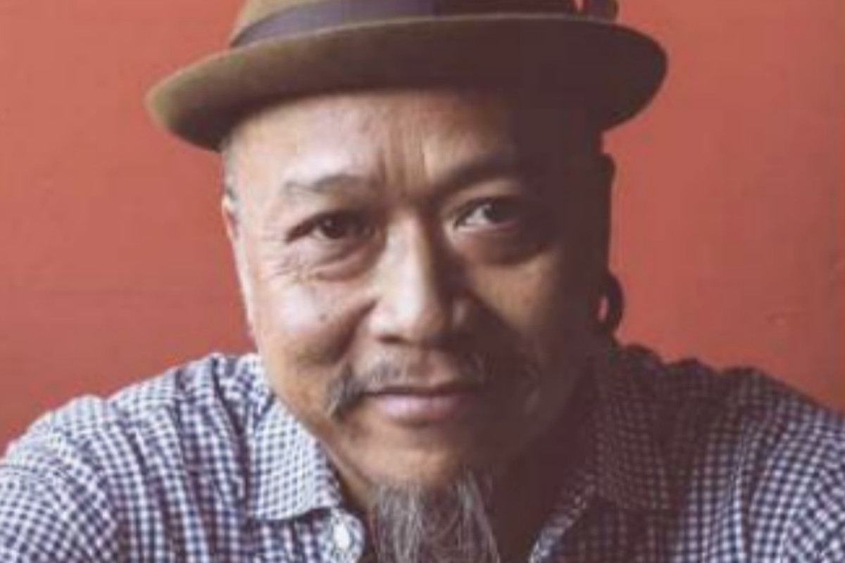 A portrait of Tom Suanpirintra in a fedora and a blue button-down checkered shirt