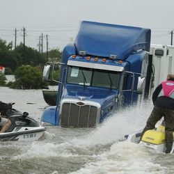 Volunteers responders jet ski around a submerged FEMA semi truck during Tropical Storm Harvey in Houston on Tuesday, Aug. 29, 2017.