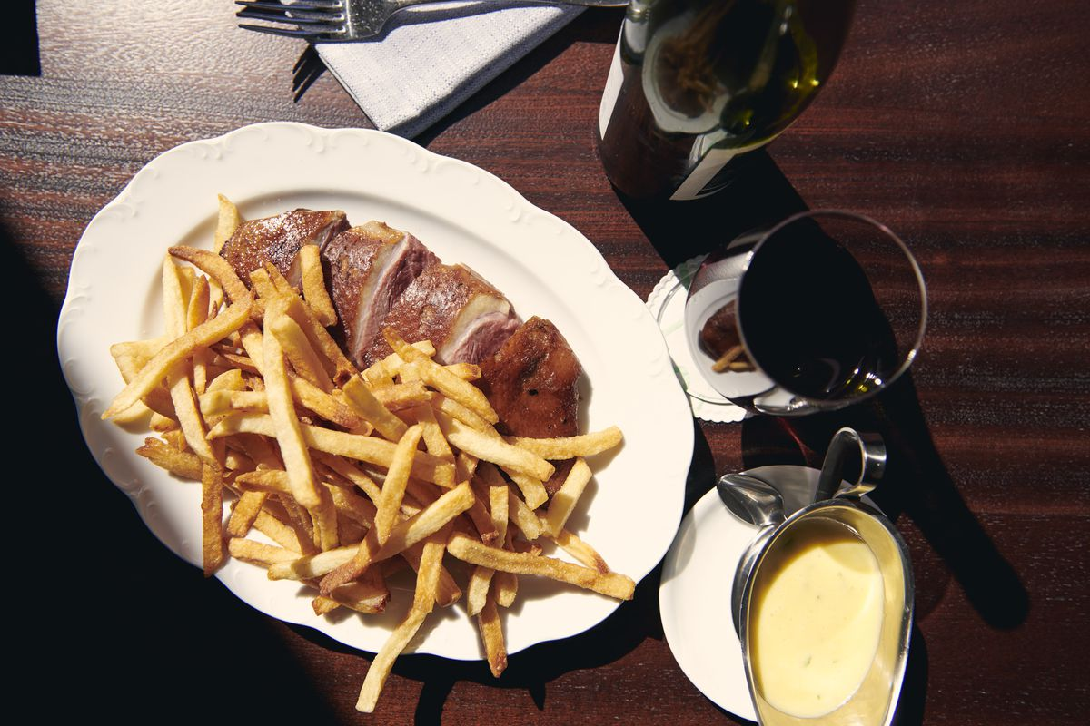 A white plate with french fries on it along with slices of duck and a yellow sauce on the side