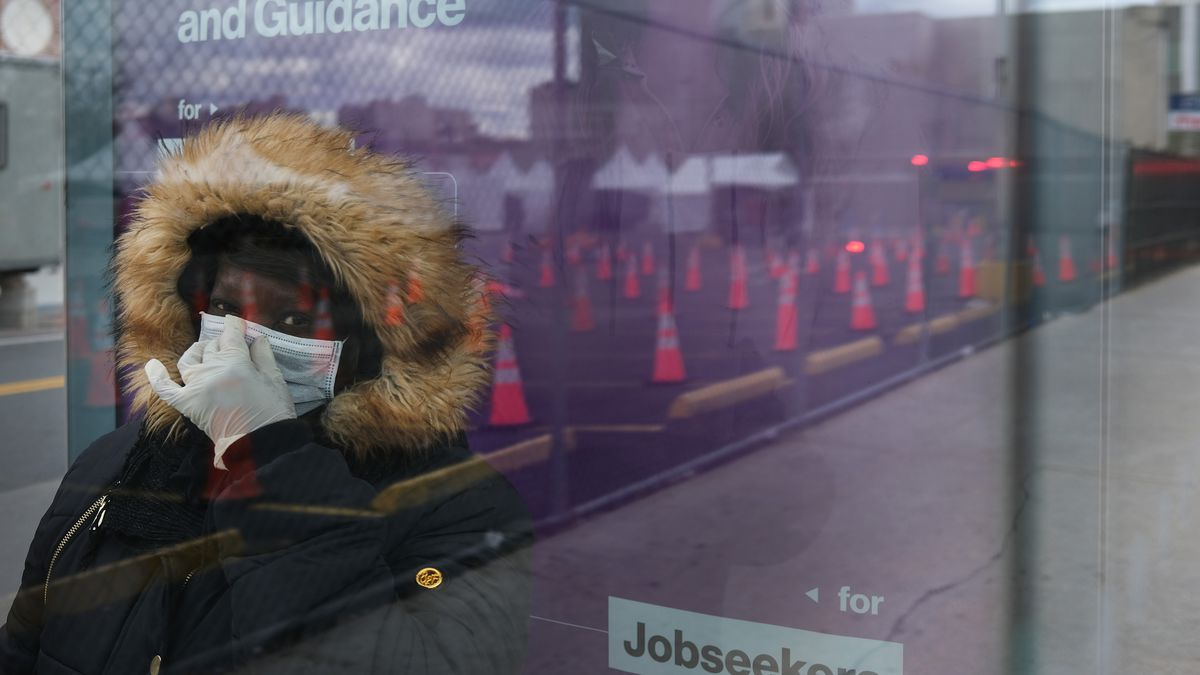 A woman wearing a mask and sitting in a glass-sided bus shelter.