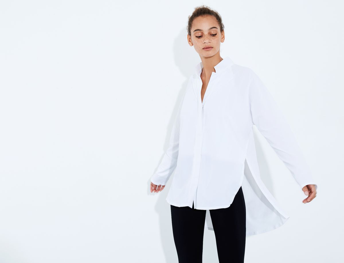A model wearing a white button down shirt and black pants