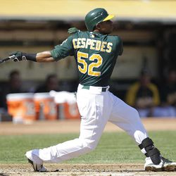 Oakland Athletics' Yoenis Cespedes swings for an RBI triple off Seattle Mariners' Erasmo Ramirez in the first inning of a baseball game Sunday, Sept. 30, 2012, in Oakland, Calif.