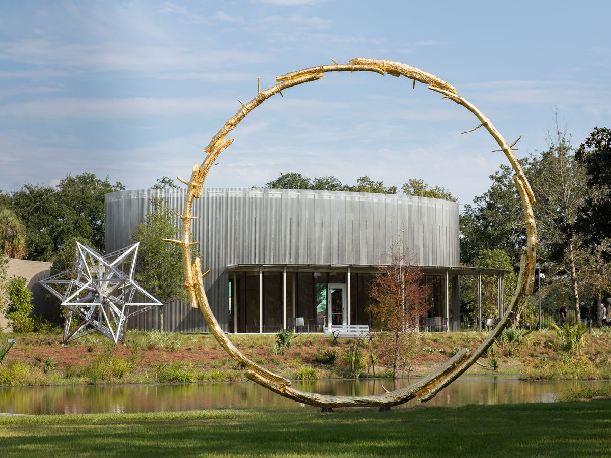 A large round circle-shaped sculpture through which a grassy vista and modern building is visible.