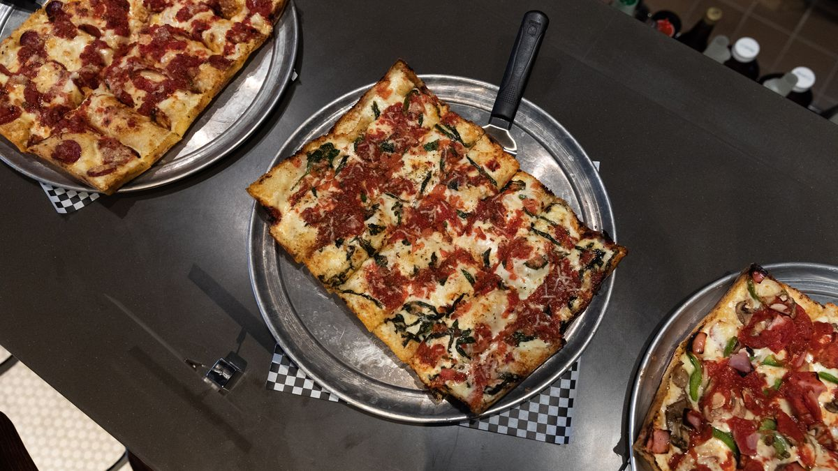 A square pizza on a metal tray with sauce on top next to two other square pizzas on metal trays.