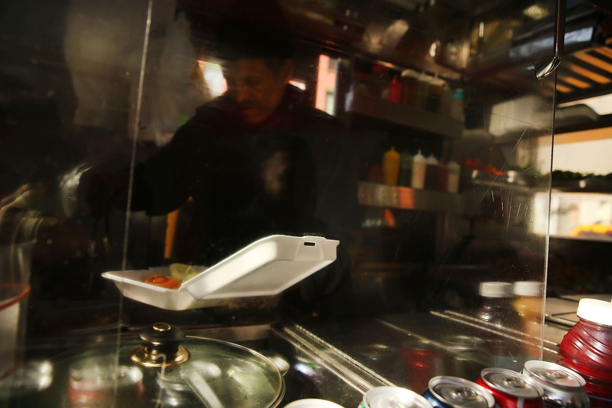 A food cart worker fills a styrofoam take-out container with food for a customer on December 19, 2013 in New York City.