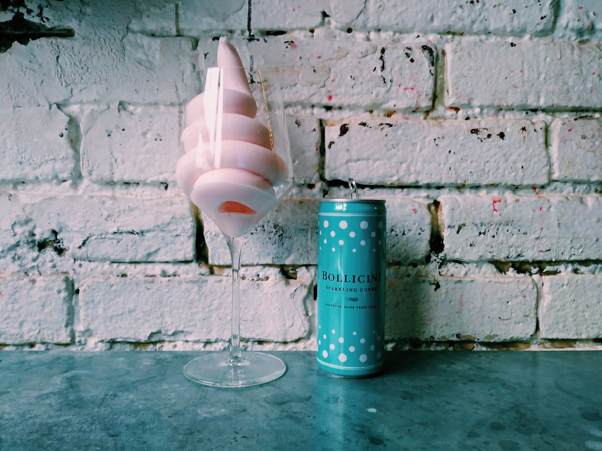 A swirl of pink soft serve is in a wine glass; a can of prosecco is next to it. Both are in front of a white brick wall.