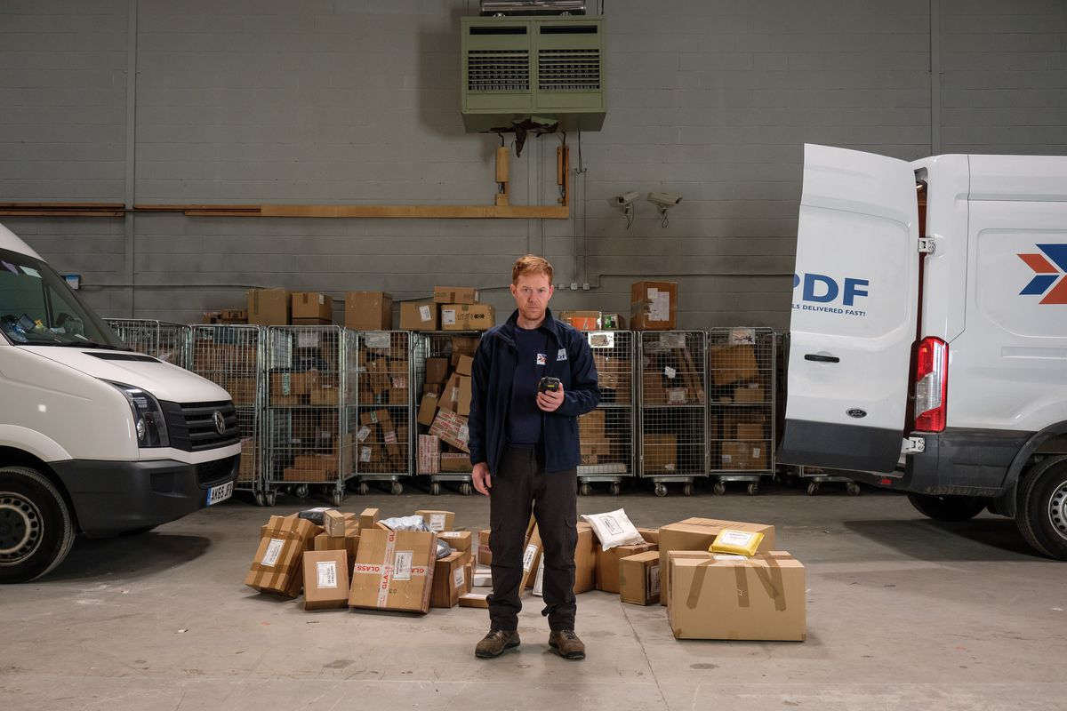 A delivery person for an Amazon-like company stands in a warehouse surrounded by packages, looking forlorn and holding a scanner, in the movie Sorry We Missed You.