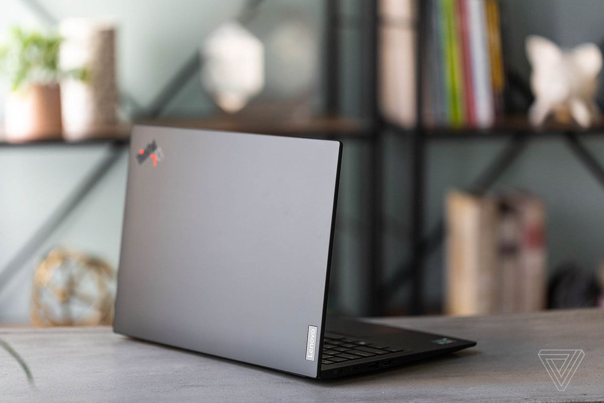 The Lenovo ThinkPad X1 Carbon Gen 9 on a table in front of a bookshelf, facing away from the camera, angled to the right.