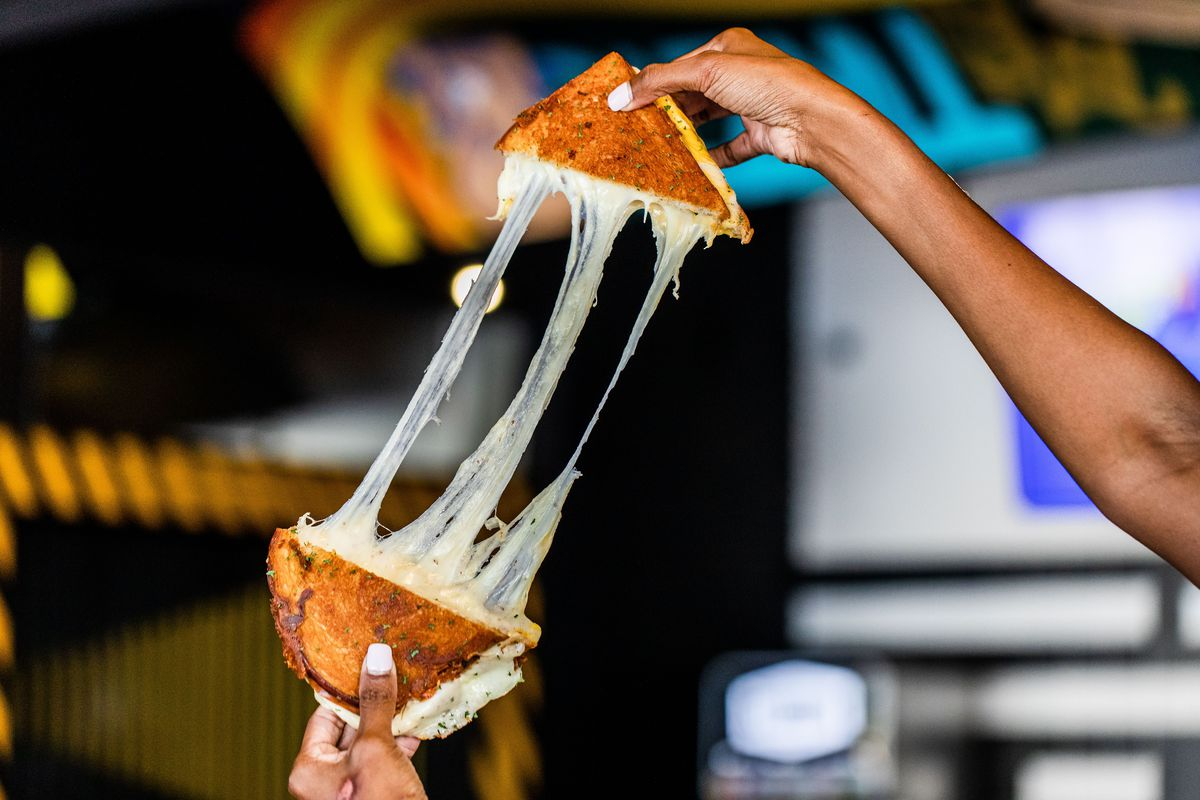 a person pulling apart two halves of a grilled cheese, with the melted cheese stretching between the halves