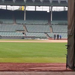 Unidentified Cubs personnel looking at the sign from near the 3B dugout inside Wrigley