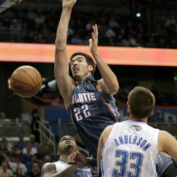 Charlotte Bobcats' Byron Mullens (22) dunks the ball as he gets between Orlando Magic's Glen Davis (11) and Ryan Anderson (33) during the first half of an NBA basketball game, Wednesday, April 25, 2012, in Orlando, Fla.