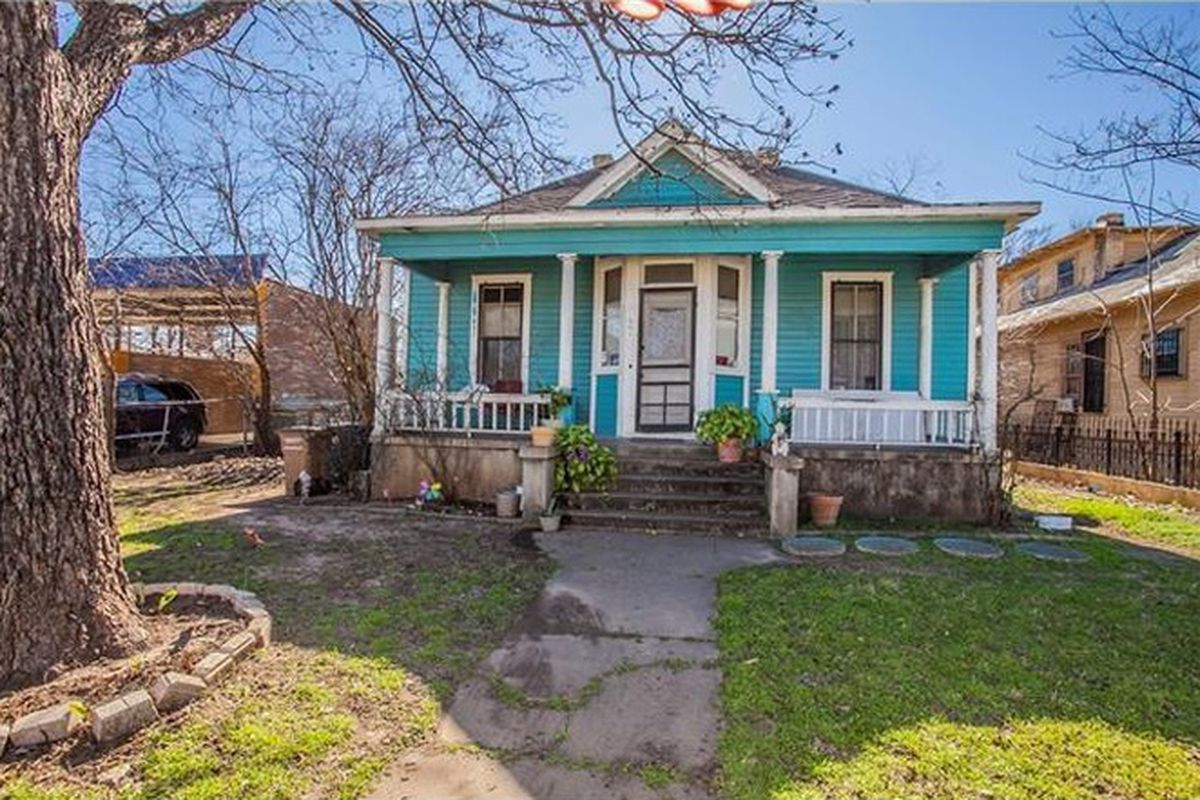 small 1910 wooden home with front porch and gabled roof over doorway, aqua with green trim