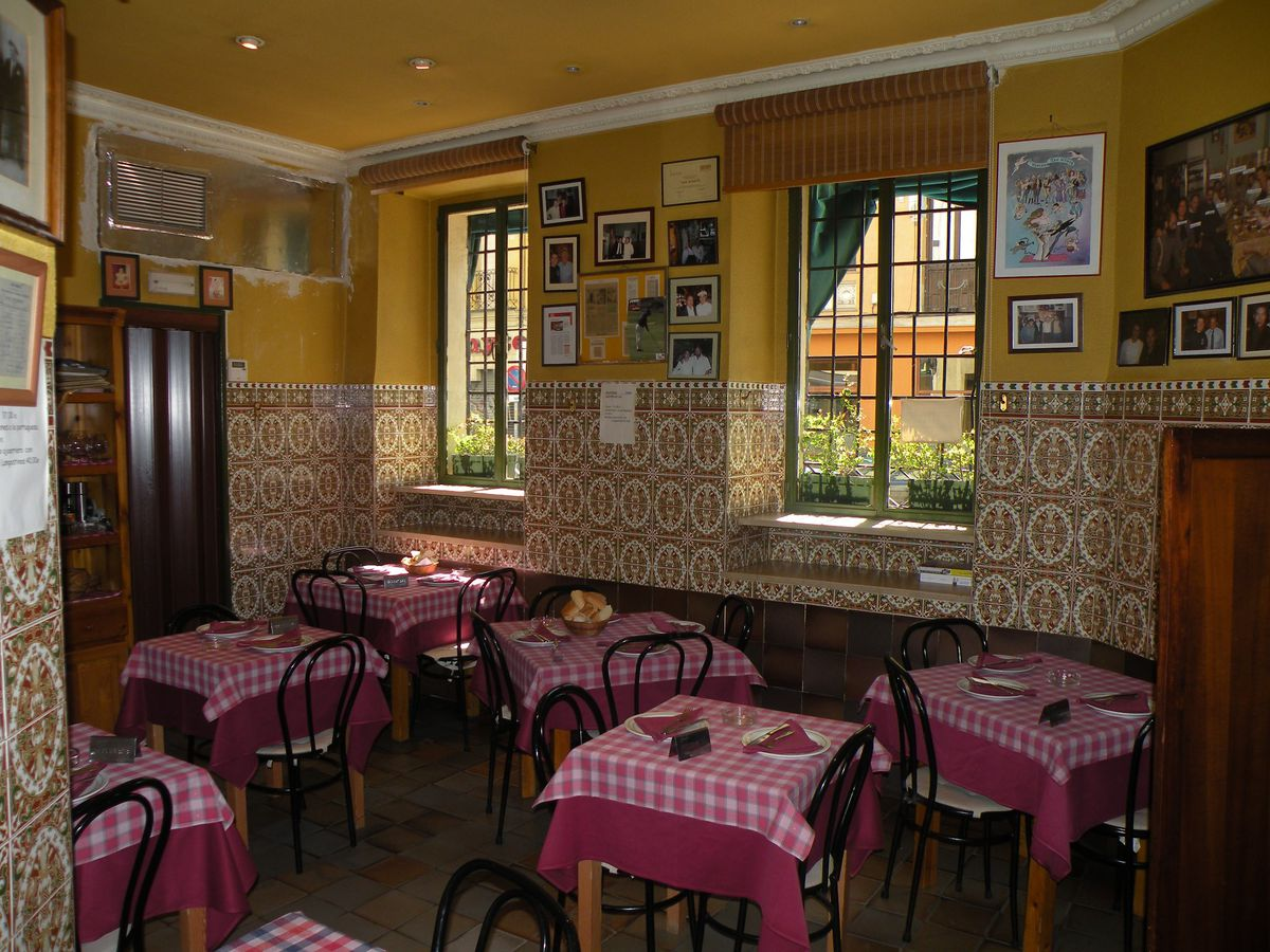 A homey restaurant interior with checkered tablecloths, many photos cluttering the walls, and soft light coming in through two windows.