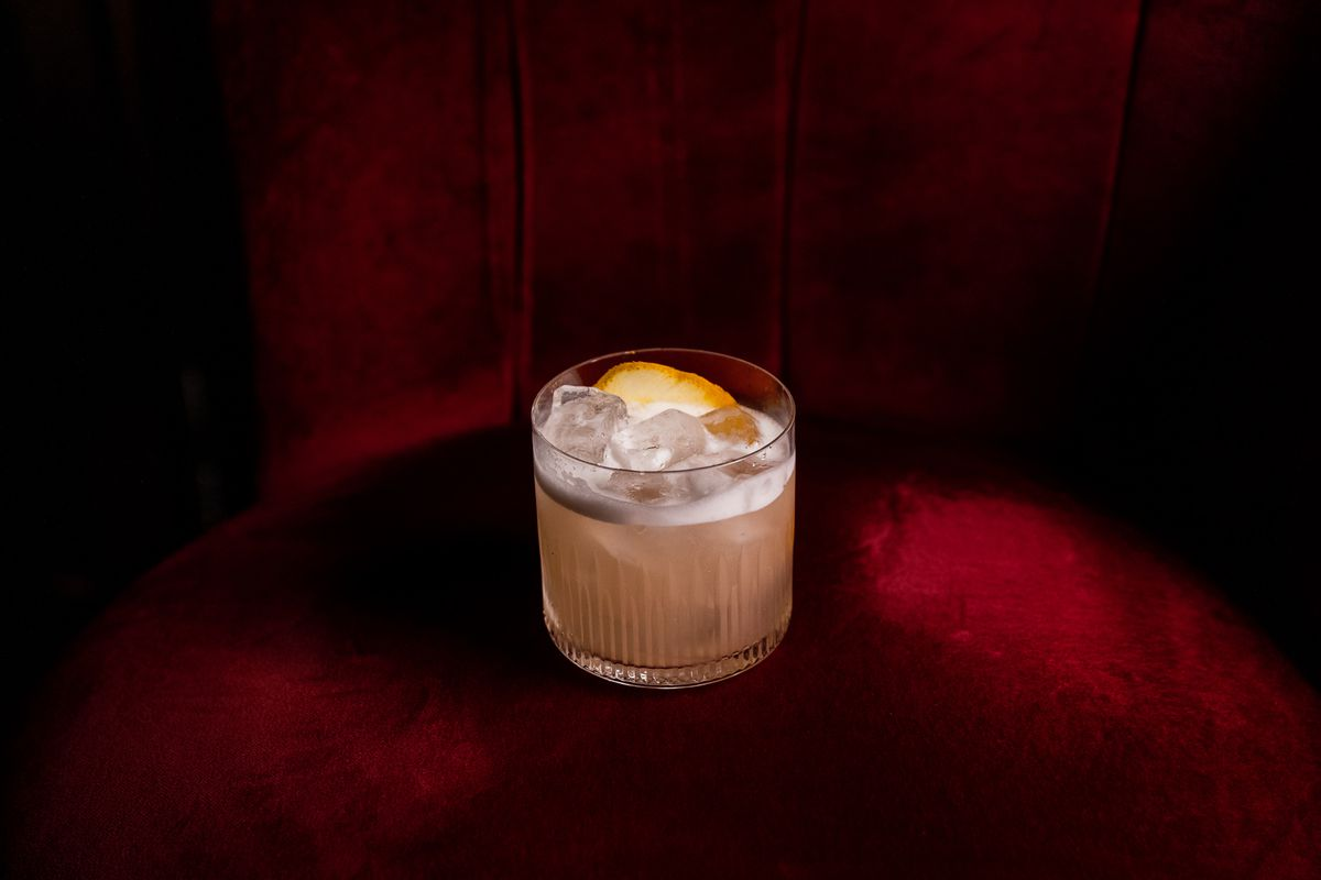 a tumbler with a pink drink with a little foam and an orange rind on a red couch