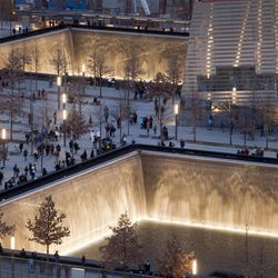 FILE - In this Dec. 20, 2011 file photo, visitors to the National September 11 Memorial in New York walk around its twin pools. The foundation that runs the memorial estimates that once the roughly $700 million project is complete, it will cost $60 million a year to operate.