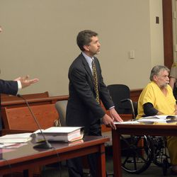 """Prosecutor Matthew Janzen, left, speaks at a sentencing hearing for Patrick Michael McCabe, 60, right, in 3rd District Judge Paul Parker's courtroom in Salt Lake City on Wednesday June 7, 2017. McCabe pleaded guilty to first-degree felony counts of murder and aggravated burglary in the December 1977 slaying of 16-year-old Sharon """"Lecia"""" Schollmeyer in her Salt Lake apartment. McCabe's defense lawyer, Mike Sikora, is standing at center."""