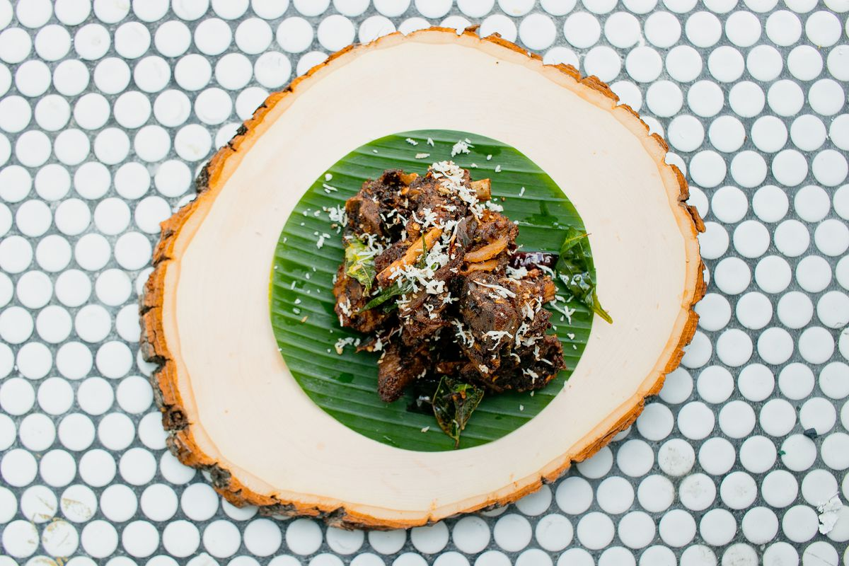 A serving of lamb set on a circular cut of banana leaf and plated on a round wooden dish.