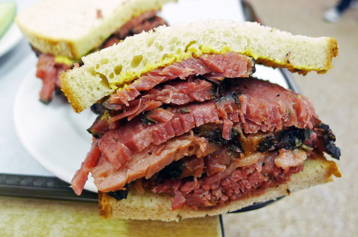 A very legit looking pastrami sandwich, thickly sliced with fat and mustard adhering.