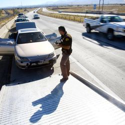 Utah Highway Patrol Troopers search a car after conducting a roadside sobriety test Wednesday, Oct. 17, 2012, on a female driver on Bangerter Highway near 1300 South. The woman was arrested for investigation of drunken driving.