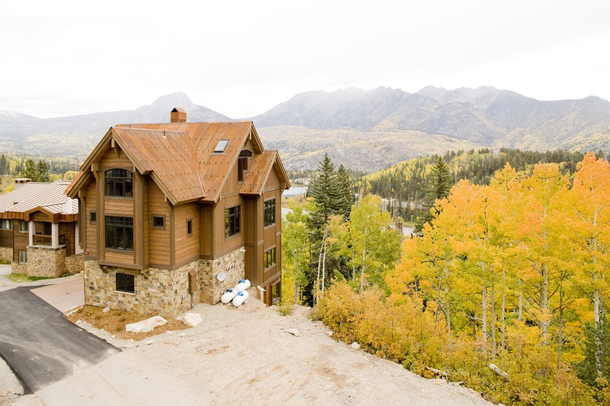 A wood and stone house sits on a ridge overlooking a valley of aspens and a river. Mountains and fog can be seen in the distance.