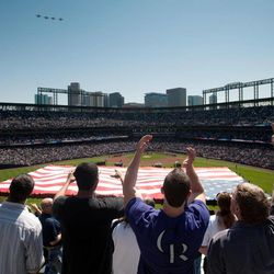 As a flyover of planes from Buckley Air Force Base heads away, fans cheer in the rockpile as the Colorado Rockies host the San Francisco Giants in the home-opening game of the 2012 season on Monday, April 9, 2012. The Giants went on to post a 7-0 victory in a baseball game.