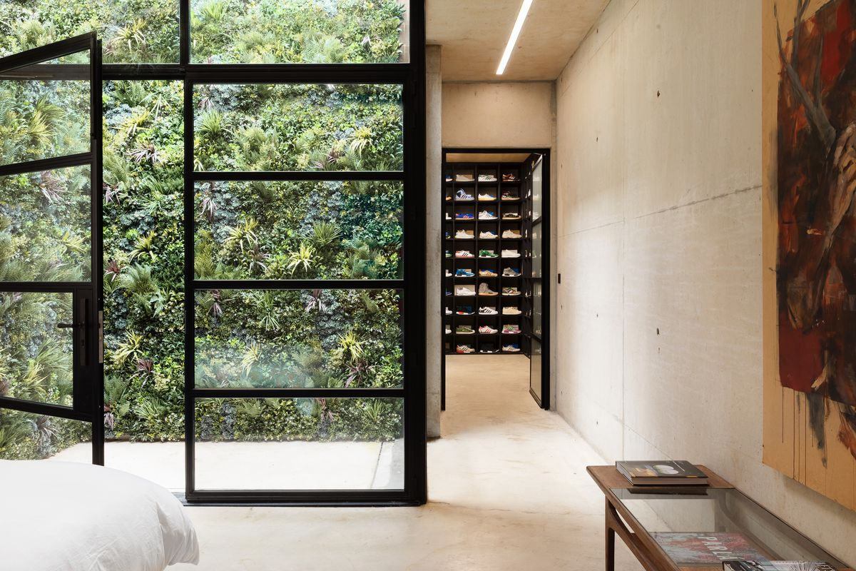 Glass doors open to a wall of vegetation.