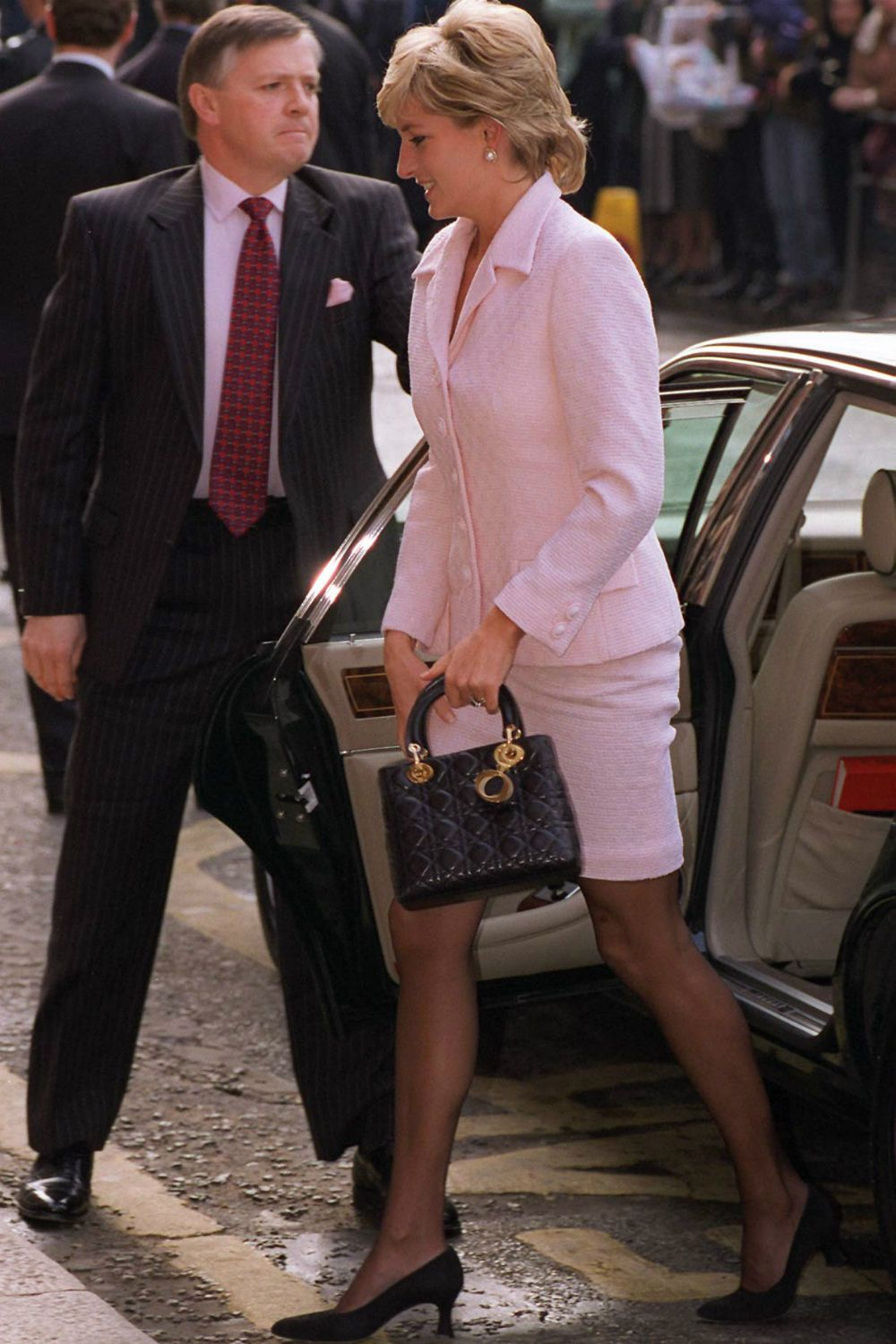 Princess Diana exiting a car in a pink suit