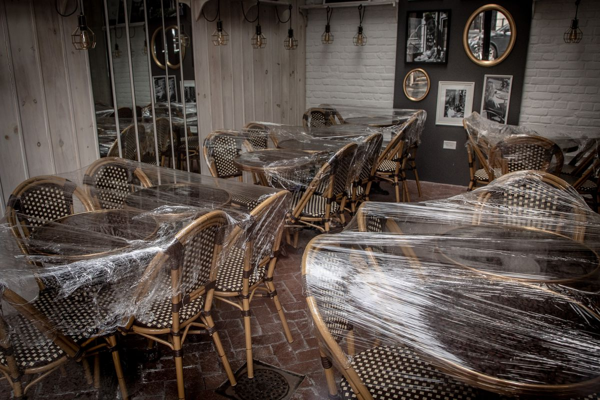 The inside of a restaurant with chairs and tables that have been covered in plastic wrapping