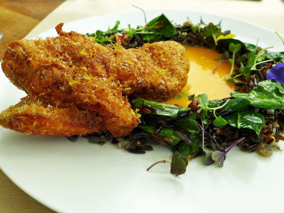 Fancy fried chicken in a yellow habanero sauce surrounded by a ring of leaves