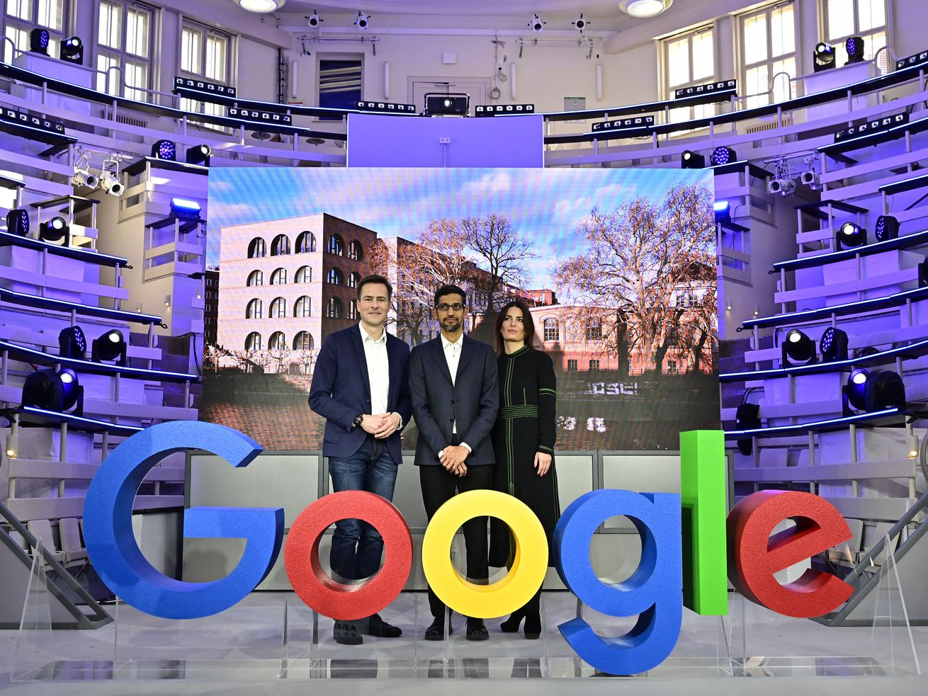 """Google CEO Sundar Pichai and other Google leaders pose for the media at the opening of a new Google office in Berlin by standing behind large letters spelling out """"Google."""""""