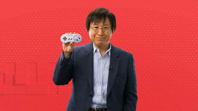 a Japanese man holding a wireless Super Nintendo Entertainment System controller
