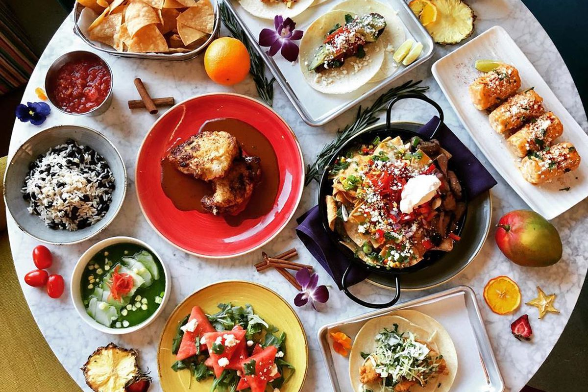 A round white table is covered with Mexican dishes, including tacos, street corn, and more