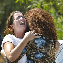 An Israeli woman is comforted after learning of the killing of a close friend in Gaza.