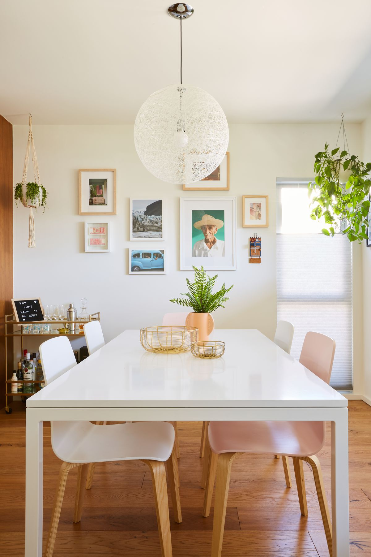 A dining room with a white table and pink and white chairs. There is a white light fixture hanging over the table. Works of art hang on one of the walls.