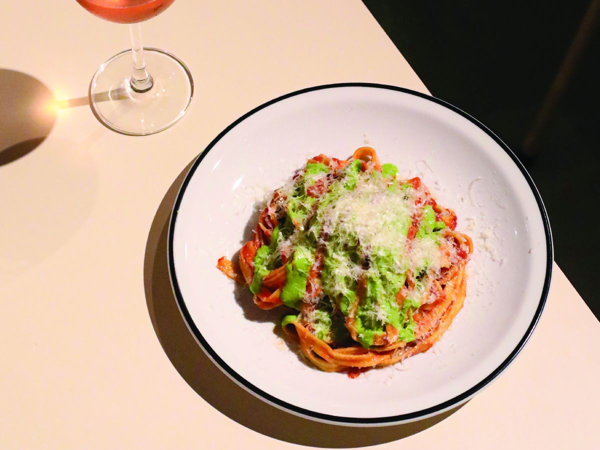 A plate of pasta with multiple sauces for topping besides a glass of rose wine
