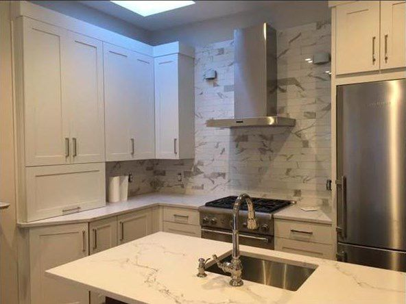 A newly done, heavily granite kitchen with an island.