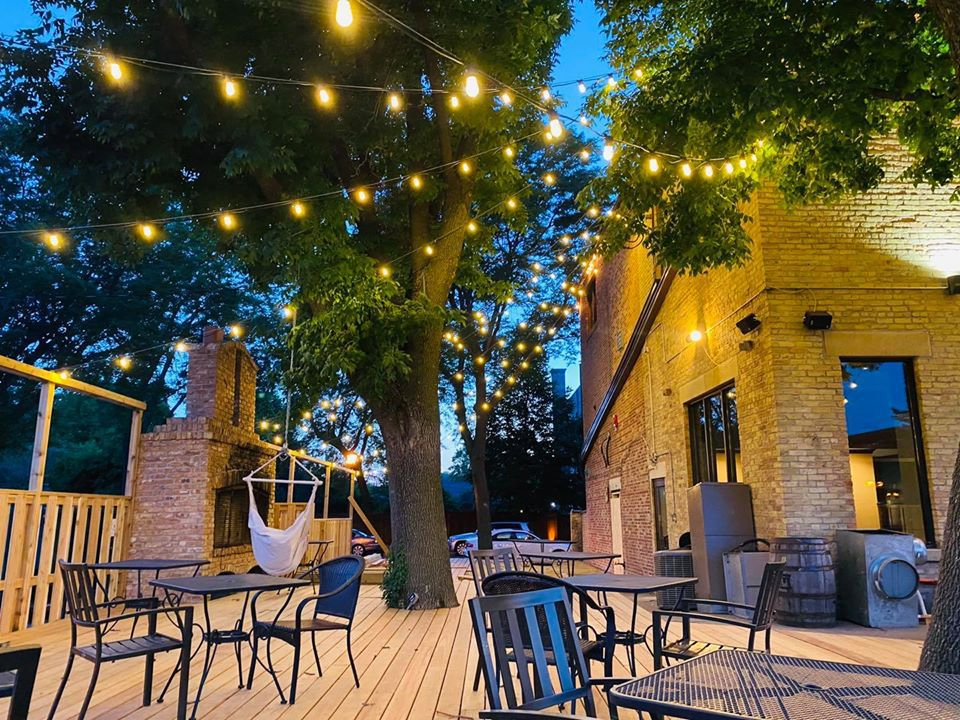 A patio at dusk, topped with bistro lights, under a tree