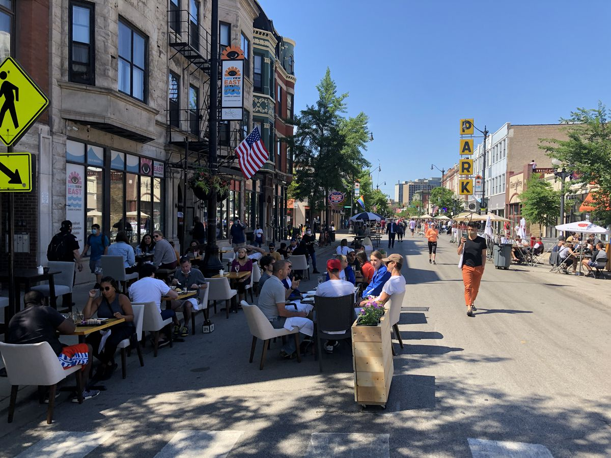 Diners eating at tables set up on the street