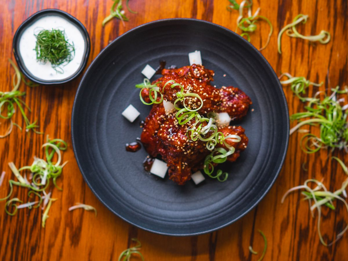 A circular dish with wing topped with scallions, and flanked by cubed radishes.